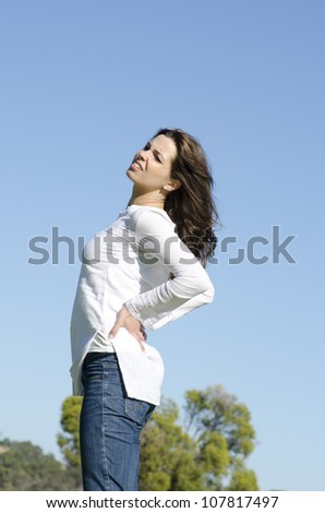 An attractive looking young woman is obviously suffering from back pain, with a stressful facial expression, clear blue sky as background and copy space. - stock photo
