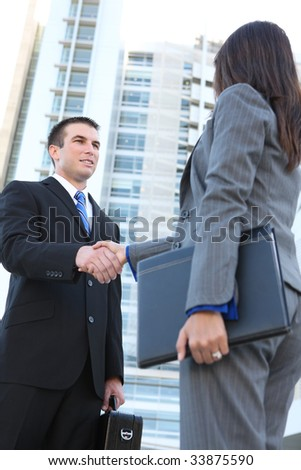 An attractive man and woman business team shaking hands at office building - stock photo