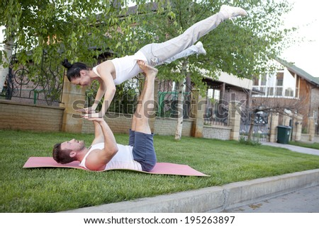 An attractive man and woman practice tantra yoga on a grass before the house - stock photo