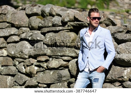 An attractive man leaning back against a big wall of rocks, wearing a light blue blazer, sunglasses and jeans, on a sunny summer day. - stock photo