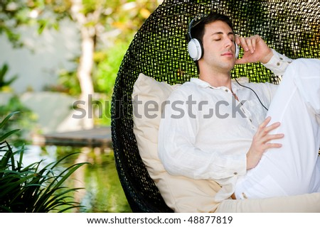 An attractive man listening to music and relaxing outdoors - stock photo