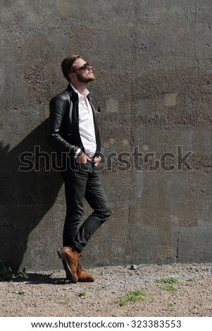 An attractive man wearing a black leather jacket and sunglasses leaning against a stone wall outside on a sunny summer day. - stock photo