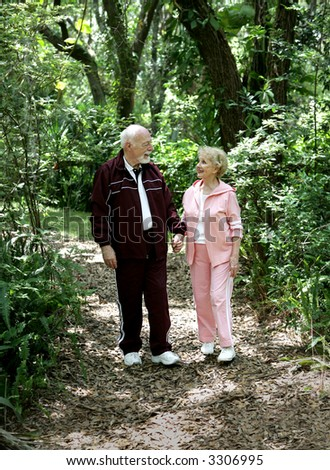 An attractive senior couple strolling through the park hand in hand. - stock photo