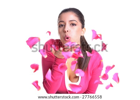 An attractive woman blowing pink rose petals from her hand, isolated on white background. Motion blur on the petals. - stock photo