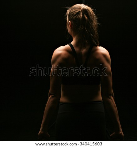 An attractive woman flexing her back on a black background - stock photo