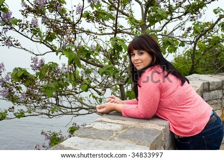 An attractive woman leans up against the wall along the historic Newport coast along the cliff walk path. - stock photo