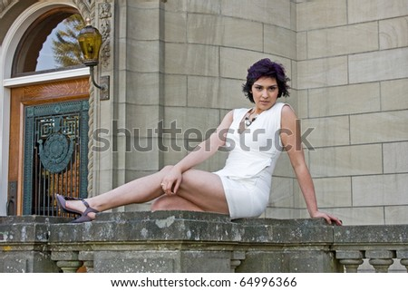 An attractive woman posing seductively on a railing. - stock photo