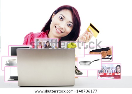 An attractive woman purchasing product online using her laptop computer and credit card, - stock photo