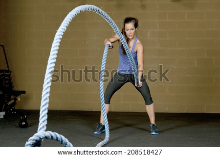 An attractive young and athletic girl using training ropes in a gym. - stock photo
