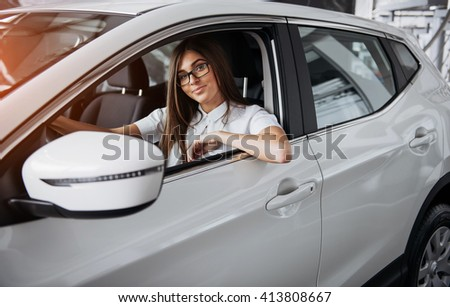 An attractive young Caucasian woman looking at the camera from the front seat of the car - stock photo