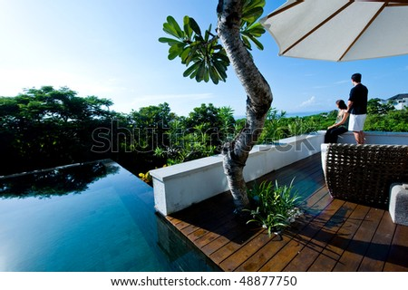 An attractive young couple relaxing by the pool outdoors - stock photo