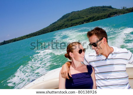 An attractive young couple relaxing outdoors together on a boat - stock photo