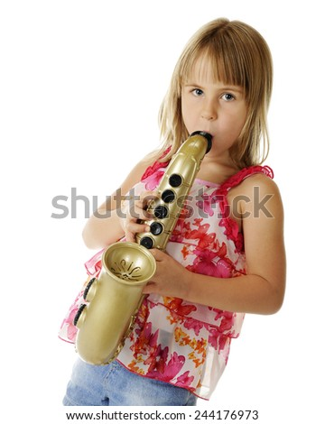 An attractive young elementary girl playing a large, toy sax.  On a white background. - stock photo