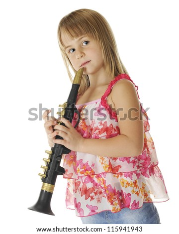 An attractive young elementary girl standing at the ready with her plastic saxophone.  On a white background. - stock photo