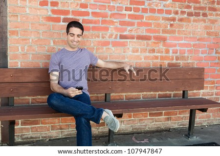 An attractive young man sitting on a bench outside using his cell phone wearing a purple shirt and jeans. - stock photo