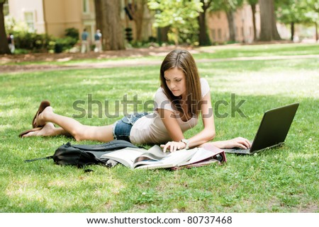 an attractive young student doing homework - stock photo