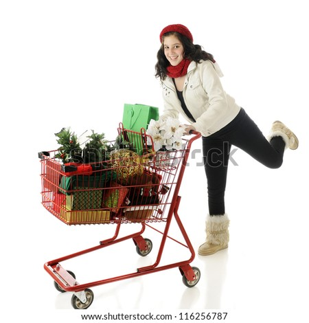 An attractive young teen running with a shopping cart filled with Christmas goodies.  On a white background. - stock photo