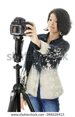 An attractive young teen shooting a selfie on a pro camera set up on a tripod.  On a white background. - stock photo