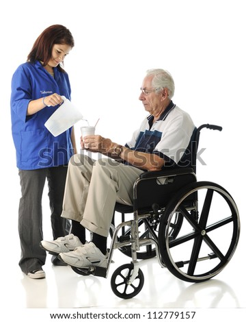 An attractive young volunteer pouring a drink for an elderly man in a wheel chair.  On a white background. - stock photo
