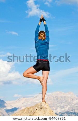 An attractive young woman doing a yoga pose for balance and stretching high in the mountains - stock photo