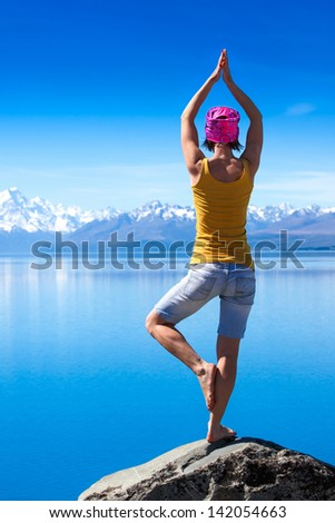 An attractive young woman doing a yoga pose for balance and stretching near the lake high in the mountains  - stock photo