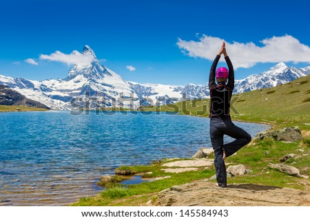 An attractive young woman doing a yoga pose for balance and stretching near the lake high in the mountains. Swiss Alps. Matterhorn - stock photo