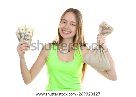 An attractive young woman holds up a bag of money while - stock photo