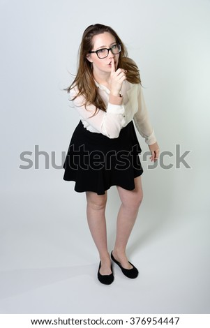 An attractive young woman in a short black skirt, white blouse, and glasses is bending forward with her finger to her lips as if to shush someone. - stock photo