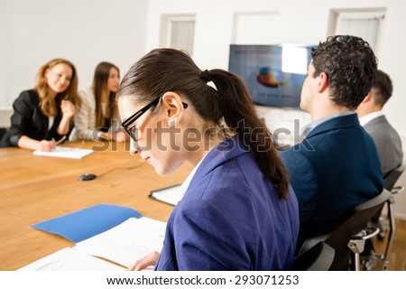 An attractive young woman is checking papers during a business meeting in a conference room - mixed caucasian team rather casual, ambiente might suggest a startup or an agency  - stock photo