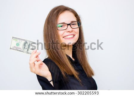 An attractive young woman is holding up a $100.00 bill and smiling at the camera. Horizontal shot. - stock photo