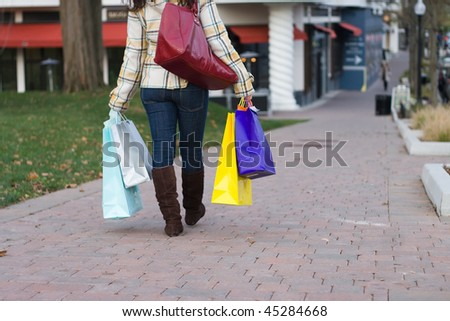 An attractive young woman out in the city carrying shopping bags.. - stock photo