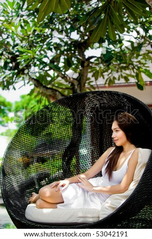 An attractive young woman relaxing and lounging outdoors - stock photo
