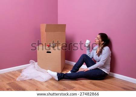 An attractive young woman takes a break during her house move - stock photo