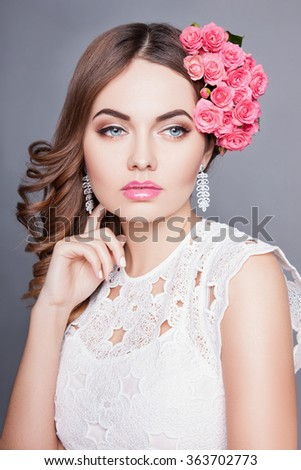 An attractive young woman with makeup on his face and flowers in her hair. Portrait of girl with dark hair on a gray background, beautiful makeup on her face.Attractive girl with perfect skin - stock photo
