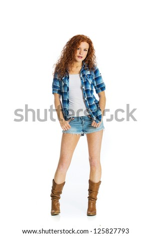 An attractive young woman with red hair and freckles wearing short denim shorts and cowboy boots. - stock photo