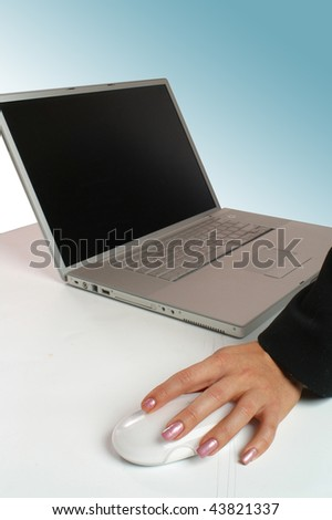 An attractive young woman working on a computer using a mouse - stock photo