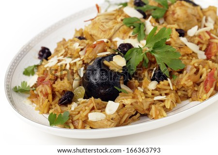 An authentic Saudi chicken kabsa (known in Qatar as majbous), garnished with raisins, parsley and almond flakes, on a serving bowl. Kabsa is a national staple for Saudi Arabia and the Arab Gulf States - stock photo