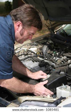 An auto mechanic working on a car. - stock photo