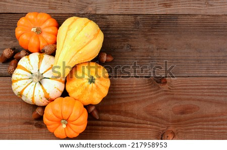 An autumn still life of decorative mini pumpkins, gourds and acorns on a rustic wood table. Horizontal format with copy space. - stock photo