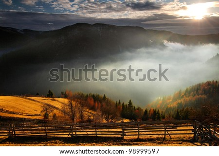 An awesome mountain landscape with sun, fog, and forrest - stock photo