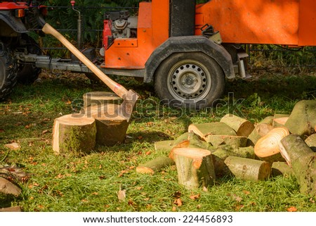 An axe in a tree stump with tree shredder in the background - stock photo