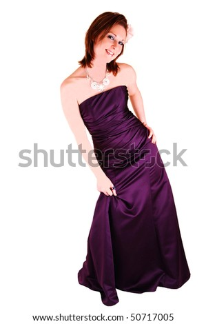 An beautiful young woman in an burgundy long evening gown standing in the  studio, looking into the camera, for white background. - stock photo
