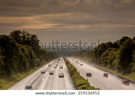 An early evening shot from a german wet highway with a poor visibility. - stock photo