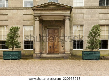 An early nineteenth century neo-classical mansion doorway and columns. Tatton hall Knutsford, Cheshire, England, United Kingdom.    - stock photo