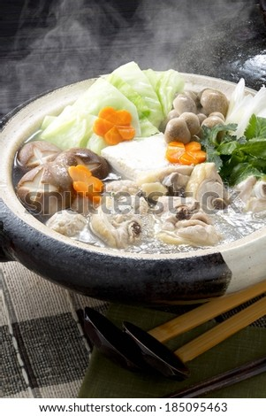 An earth ware hotpot filled with mushrooms, cabbage, carrots and chicken. - stock photo