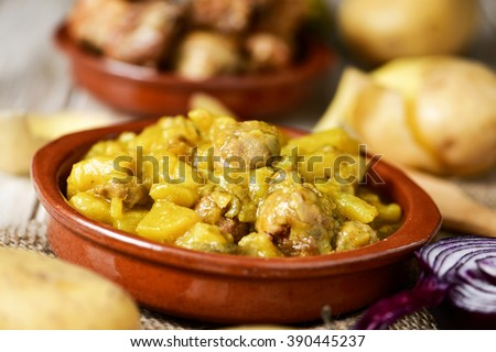 an earthenware bowl with a spanish guiso de patatas con albondigas, a stew with potatoes and meatballs, on a table with some raw vegetables - stock photo
