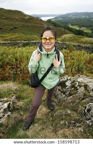 An East Asian Woman, looking at the camera, hiking in Lake District, Cumbria, UK. Grasmere lake in the back ground.   - stock photo