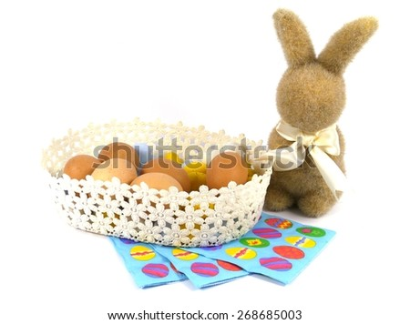 An Easter bunny and a basket with boiled chicken eggs  - stock photo