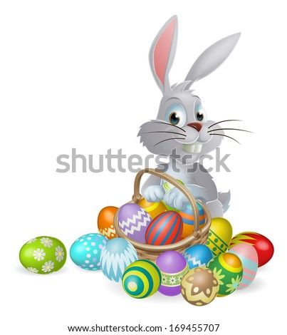 An Easter bunny white rabbit with a basket of painted chocolate Easter eggs - stock photo