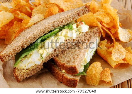 An egg salad sandwich with barbecued potato chips on brown paper - stock photo